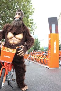 Sasquatch riding his BIKETOWN in Downtown Portland.