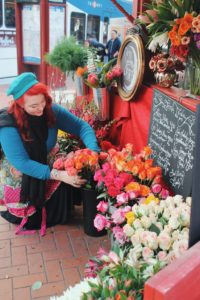 Local business owner prepping her flower stand in downtown.